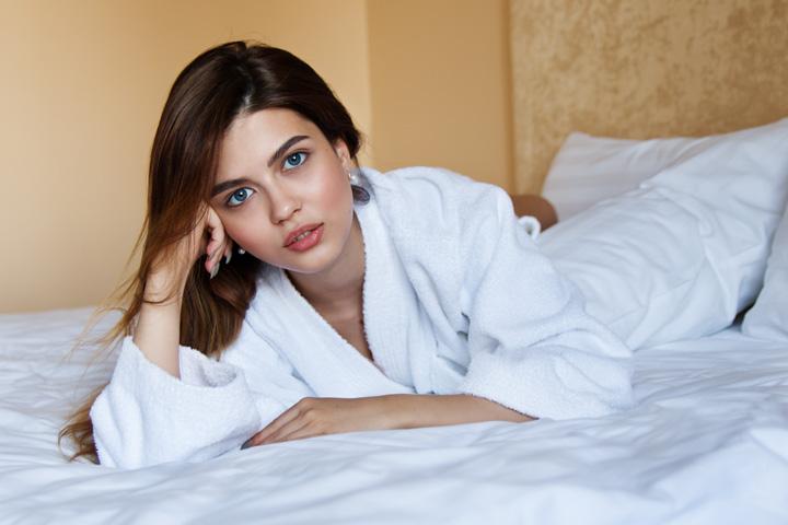 バスローブ姿でベッドに横になる白人女性